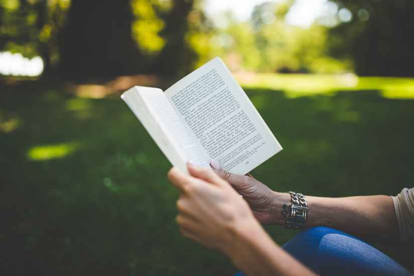person holding and reading book during daytime