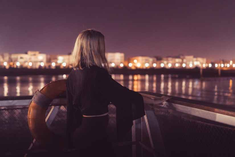 woman standing near body of water during night time